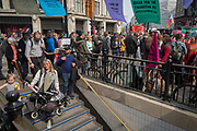 As activists with Extinction Rebellion protest about climate change in a blocked-off Oxford Circus, commuters descend the steps into the underground, on 17th April 2019, in London, England.