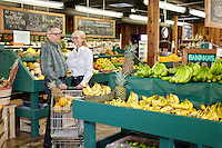 Happy couple standing with shopping cart in produce market