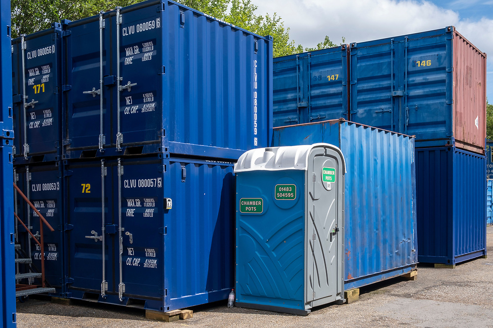 A portable toilet unit next to two rows of stacked blue metal storage shipping containers in a self-storage depot in Aldershot, Hampshire, UK.   (photo by Andrew Aitchison / In pictures via Getty Images)