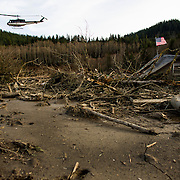 A rescue helicopter flies over the wreckage of homes and lives destroyed by a mudslide near Oso, Wash. Photographed on Monday, March 24, 2014 near Oso, Wash. (Joshua Trujillo, seattlepi.com)