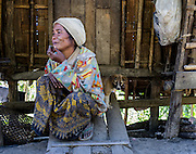 A woman with her small puppy smokes outside her home in Chin State, Myanmar.