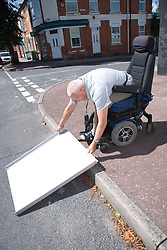 Male wheelchair user laying down a portable folding travel ramp to use at a roadside kerb,