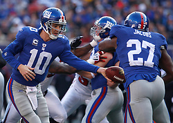 Nov 22, 2009; East Rutherford, NJ, USA; New York Giants quarterback Eli Manning (10) hands the ball to New York Giants running back Brandon Jacobs (27) during the first half of their game against the Atlanta Falcons at Giants Stadium. Mandatory Credit: Ed Mulholland