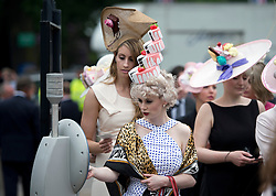 © London News Pictures. 20/06/2013. Ascot, UK.  Racegoers wearing elaborate hats enter the turnstiles on Ladies Day on day three of Royal Ascot at Ascot racecourse in Berkshire, on June 20, 2013.  The 5 day showcase event,  which is one of the highlights of the racing calendar, has been held at the famous Berkshire course since 1711 and tradition is a hallmark of the meeting. Top hats and tails remain compulsory in parts of the course. Photo credit should read: Ben Cawthra/LNP