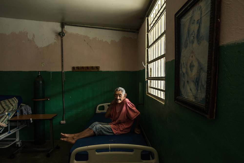 BARQUISIMETO, VENEZUELA - JULY 28, 2016: The economic crisis that has left Venezuela with little hard currency has also severely affected its public health system, crippling hospitals like El Pampero Psychiatric Hospital by leaving it without the resources it needs to take care of patients living there, the majority of whom have been abandoned by their families and rely completely on the state to meet their basic needs. The hospital has not employed a psychiatrist for over two years. The halls are filled with sounds of patients crying or screaming, and an overpowering stench of urine and feces.  Drugs used to combat bipolar disorder, epilepsy, schizoaffective disorder and chronic anxiety are now in short supply, as are numerous sedatives and tranquilizers needed to care for patients. Members of the nursing staff debate daily which patients are the most unstable, to decide which patients will receive pills and which will go without. When a patient loses control, often the only thing they can do is lock them in an isolation cell to prevent them from hurting themselves, other patients and members of the staff. The hospital does not even have basic hygiene or cleaning supplies.  There is no soap, no shampoo, no tooth paste, no toilet paper.  Patients relieve themselves in the common areas and patio area, and clean themselves only with water. Nearly every patient is infected with scabies because they do not have the resources to bathe properly or to have their threadbare, misfitted clothes washed as often as needed. To make matters worse, the hospital only has running water a few hours a day.  PHOTO: Meridith Kohut for The New York Times