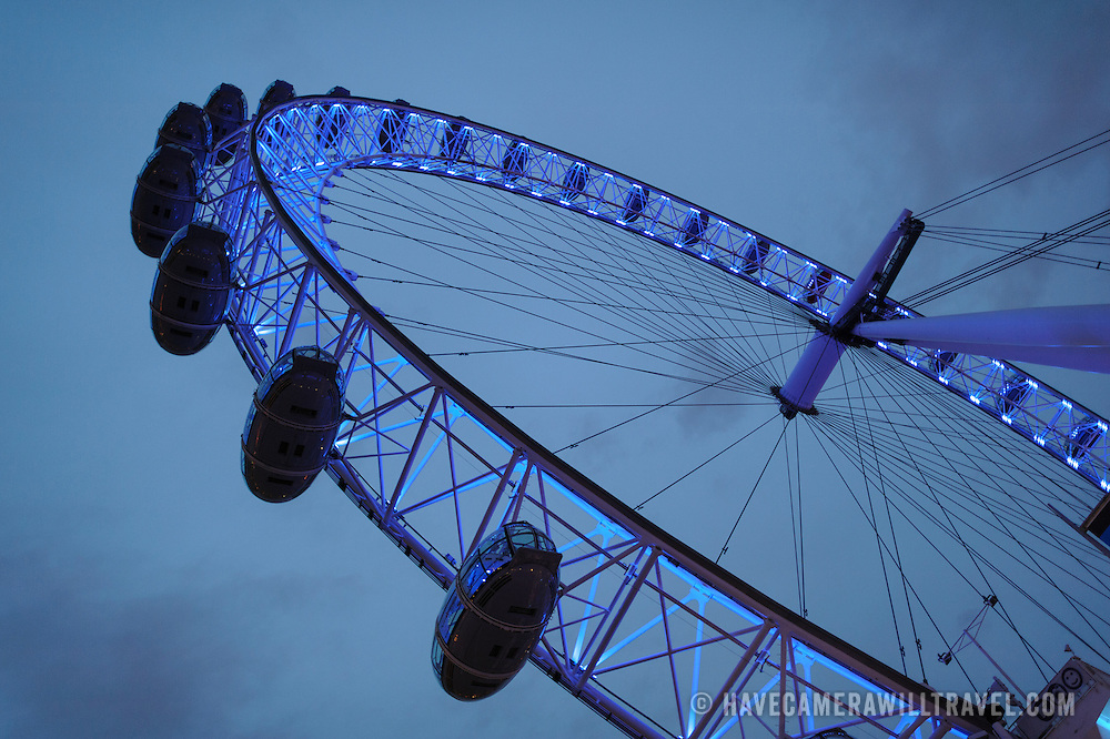 The London Eye (formerly known as the Millenium Wheel) at dusk against an overcast sky.