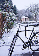 Old fashioned bicycle and winter snow scenic image of a suburban back garden, Oxford UK