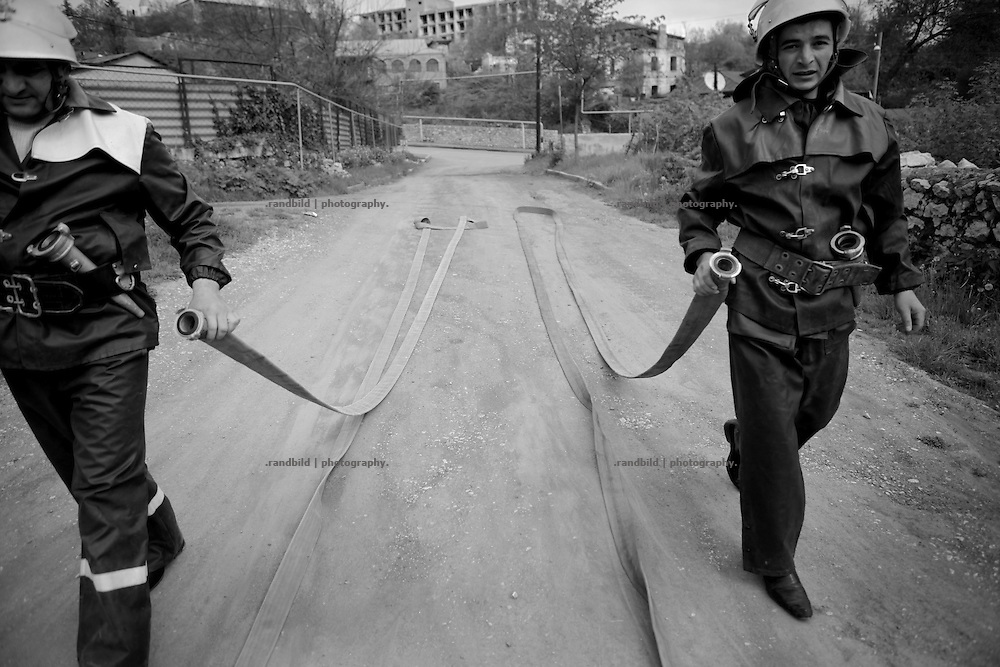 "Shushi firefighters during an exercise at their headquarters in Shushi. This image is part of the photoproject ""The Twentieth Spring"", a portrait of caucasian town Shushi 20 years after its so called ""Liberation"" by armenian fighters. In its more than two centuries old history Shushi was ruled by different powers like armeniens, persians, russian or aseris. In 1991 a fierce battle for Karabakhs independence from Azerbaijan began. During the breakdown of Sowjet Union armenians didn´t want to stay within the Republic of Azerbaijan anymore. 1992 armenians manage to takeover ""ancient armenian Shushi"" and pushed out remained aseris forces which had operate a rocket base there. Since then Shushi became an ""armenian town"" again. Today, 20 yeras after statement of Karabakhs independence Shushi tries to find it´s opportunities for it´s future. The less populated town is still affected by devastation and ruins by it´s violent history. Life is mostly a daily struggle for the inhabitants to get expenses covered, caused by a lack of jobs and almost no perspective for a sustainable economic development. Shushi depends on donations by diaspora armenians. On the other hand those donations have made it possible to rebuild a cultural centre, recover new asphalt roads and other infrastructure. 20 years after Shushis fall into armenian hands Babies get born and people won´t never be under aseris rule again. The bloody early 1990´s civil war has moved into the trenches of the frontline 20 kilometer away from Shushi where it stuck since 1994. The karabakh conflict is still not solved and could turn to an open war every day. Nonetheless life goes on on the south caucasian rocky tip above mountainious region of Karabakh where Shushi enthrones ever since centuries."