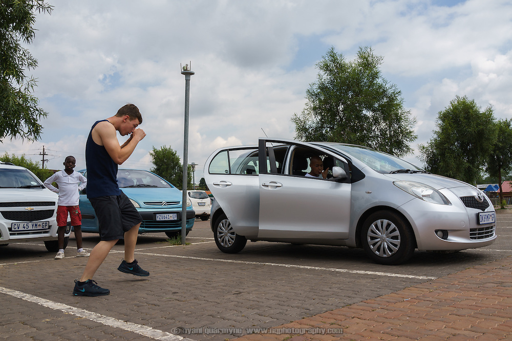 Joe Eades, who is coached by Julie Tshabalala, South African women's welterweight and middleweight champion, shadow boxing next to Tshabalala's car as they wait for an amateur boxing tournament to begin in Cosmo City, a large low-income housing development 40 minutes north of Johannesburg, South Africa. It will be Eades' first fight.