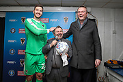 AFC Wimbledon goalkeeper Joe Day (21) receiving man of match award and patting Ivor Heller on the head during the EFL Sky Bet League 1 match between AFC Wimbledon and Ipswich Town at the Cherry Red Records Stadium, Kingston, England on 11 February 2020.