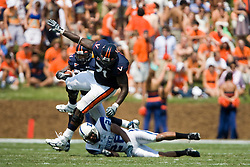Virginia guard Branden Albert (71) blocks Duke safety Adrian Aye-Darko (28) to clear a path for Cedric Peerman (37).  The Virginia Cavaliers defeated the Duke Blue Devils 23-14 at Scott Stadium in Charlottesville, VA on September 8, 2007  With the loss, Duke extended their longest-in-the-nation losing streak to 22 games.