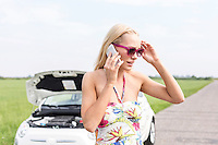 Tensed woman using cell phone on country road with broken down car in background