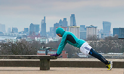 Primrose Hill, London, February 15th 2015. A man does push-ups with the skyline of the City providing a backdrop on a chilly early morning on Primrose Hill, overlooking London&rsquo;s skyline.<br /> ///FOR LICENCING CONTACT: paul@pauldaveycreative.co.uk TEL:+44 (0) 7966 016 296 or +44 (0) 20 8969 6875. &copy;2015 Paul R Davey. All rights reserved.