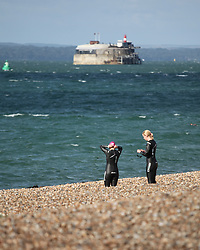 © Licensed to London News Pictures. 09/08/2014. Southsea, Hampshire, UK. Two women about to venture into the sea for a morning swim in Southsea, Hampshire this morning, 9th August 2014. The weather is set to be sunny but breezy in the south of England today, with rain and strong winds forecast for tomorrow. Photo credit : Rob Arnold/LNP