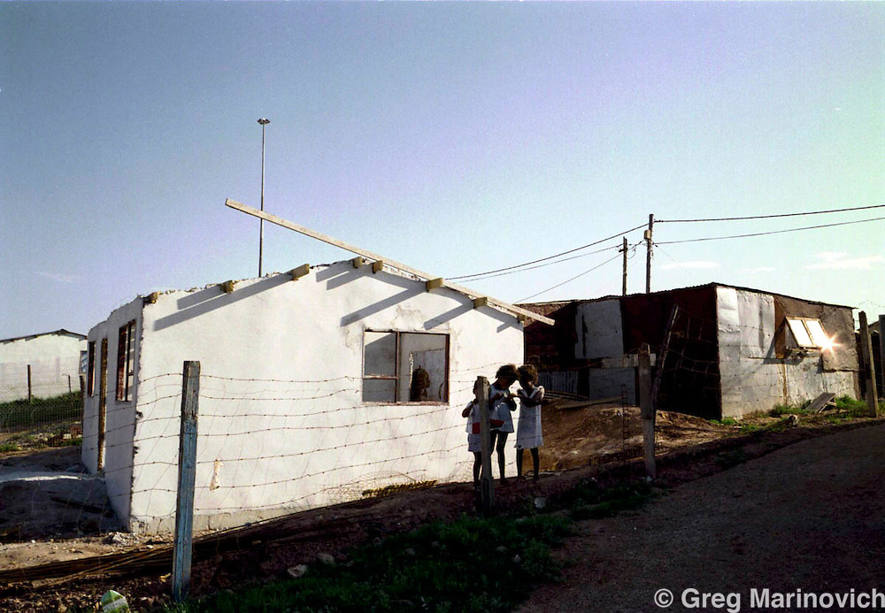 IPMG0349 South Africa, Kwa Nobuhle, 1999: The Matshaka children play next to the partially constructed house alongside the shack they inhabit before they got their new house built after three years at Kwa Nobuhle township outside Uitenhage Nov. 1999.  They used to live in a corrugated iron shack, but the South African government's housing policy and subsidies made it possible for them to get a low-cost housing unit on land they now own title deed to. .Photograph by Greg Marinovich/South Photographs