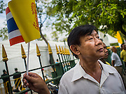 02 DECEMBER 2014 - BANGKOK, THAILAND: A man watches military units march down Ratchadamnoen Ave during the Trooping of the Colors in Bangkok. The Thai Royal Guards parade, also known as Trooping of the Colors, occurs every December 2 in celebration of the birthday of Bhumibol Adulyadej, the King of Thailand. The Royal Guards of the Royal Thai Armed Forces perform a military parade and pledge loyalty to the monarch. Historically, the venue has been the Royal Plaza in front of the Dusit Palace and the Ananta Samakhom Throne Hall. This year it was held on Sanam Luang in front of the Grand Palace.    PHOTO BY JACK KURTZ