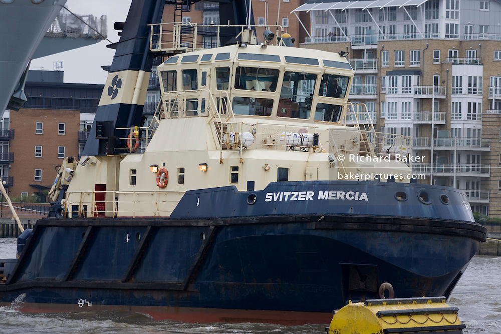 The tug and firefighting boat Svertzer Mercia pulling the Royal Navy carrier HMS Oceam on its journey up the Thames.