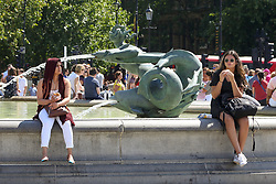 August 1, 2018 - London, London, United Kingdom - Hot And Sunny Day in London. ..Two women sitting on edge of the fountain in Trafalgar Square enjoying the hot and sunny weather in the capital. According to The Met Office the heatwave is to return after a brief drop in temperature and rainfall in the UK as 32 degrees celsius is forecasted for the coming weekend. (Credit Image: © Dinendra Haria/i-Images via ZUMA Press)