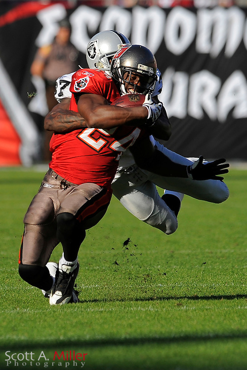 Tampa, Fl: Dec 28, 2008 -- Tampa Bay Buccaneers running back Carnell Williams (24) is tackled by Oakland Raiders cornerback Chris Johnson (37) during the Buccaneers game against the Raiders at Raymond James Stadium. Williams was injurred on the play and left the game....©2008 Scott A. Miller
