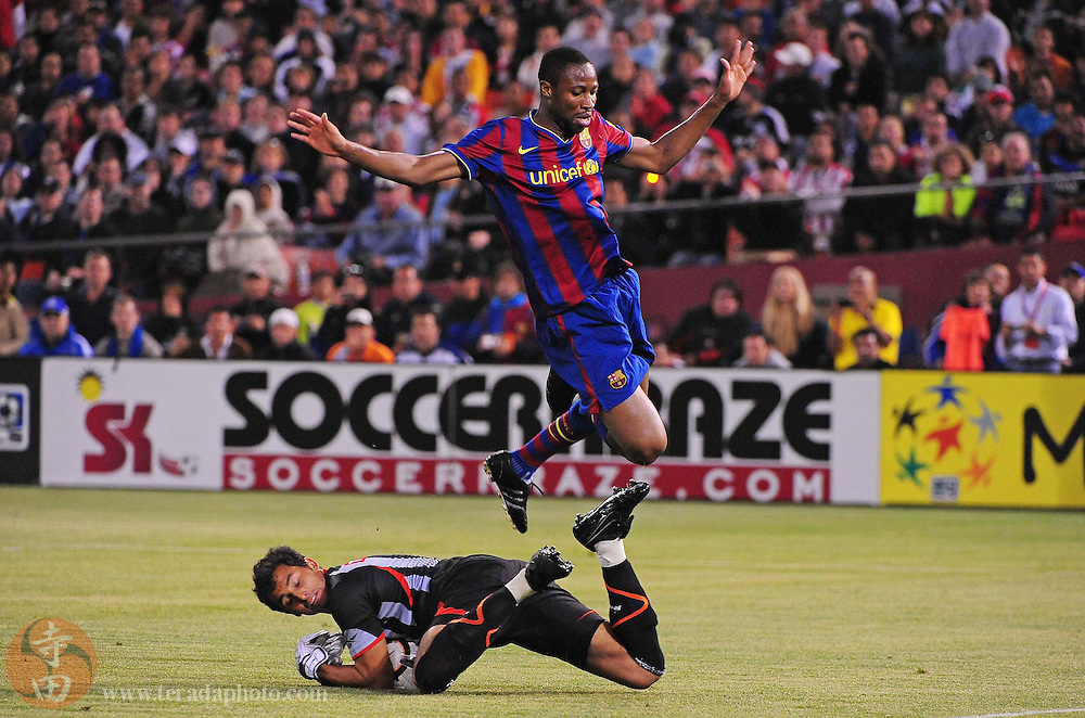 August 8, 2009; San Francisco, CA, USA; FC Barcelona midfielder Seydou Keita (top) jumps over Chivas de Guadalajara goalkeeper Luis Michel (bottom) after a save during the first half in the Night of Champions international friendly contest at Candlestick Park.