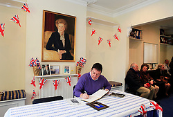 © Licensed to London News Pictures 10/04/2013.Brendon MCParland, from Loughton in Essex, signs the condolence book following the death of Margaret Thatcher, whilst others wait their turn, at Finchley Conservatives Association in north London..London, UK.Photo credit: Anna Branthwaite