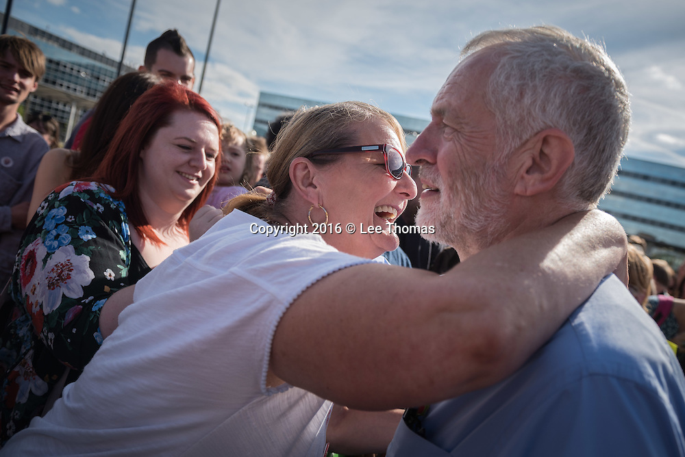 Station Square, Milton Keynes, Buckinghamshire, UK. 13th August 2016. Leader of the Labour Party Jeremy Corbyn attends a rally of hundreds of supporters at Station Square in Milton Keynes. Pictured:  A Jeremy Corbyn supporter gives the Labour leader a hug. // Lee Thomas, Flat 47a Park East Building, Bow Quarter, London, E3 2UT. Tel. 07784142973. Email: leepthomas@gmail.com. www.leept.co.uk (0000635435)