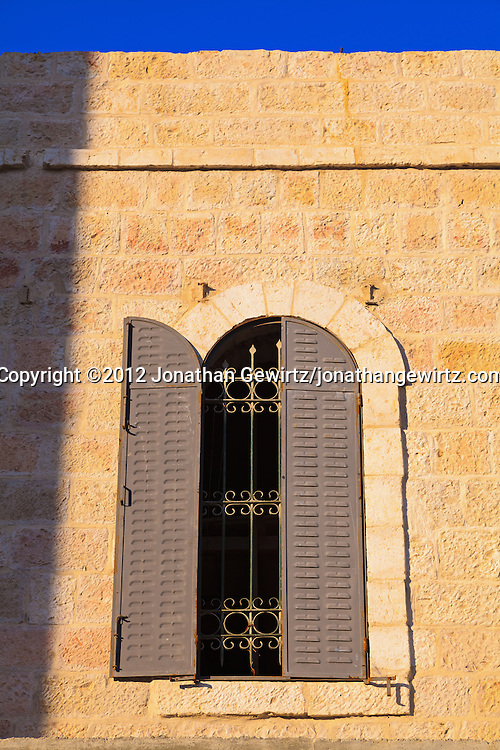 A metal-shuttered window in a building made from Jerusalem stone. WATERMARKS WILL NOT APPEAR ON PRINTS OR LICENSED IMAGES.