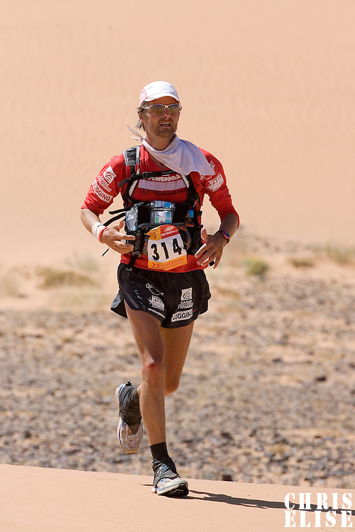 30 March 2007: #314 Philippe Remond of France runs in erg Znaigui en route to check point 3 during fifth stage of the 22nd Marathon des Sables between west of Kfiroun and erg Chebbi (26.22 miles). The Marathon des Sables is a 6 days and 151 miles endurance race with food self sufficiency across the Sahara Desert in Morocco. Each participant must carry his, or her, own backpack containing food, sleeping gear and other material.