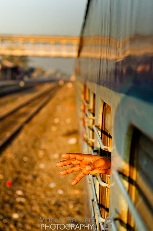 a hand out of a sleeper class train window, bijapur, india