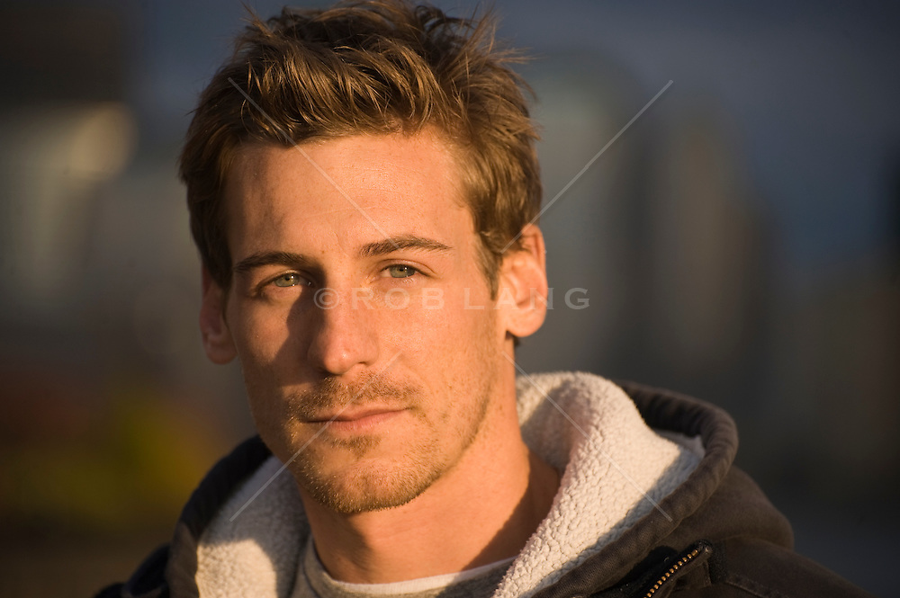Portrait of a young man with facial hair wearing a hooded sweatshirt