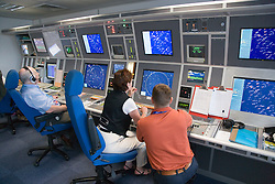 Air Traffic Control Tower Operators watching radar screens at East Midlands Airport,