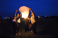 Cipriano Garrido, of Jamison, Pennsylvania (right) along with family and friends lights a lantern before releasing it into the air during the Lanterns of Hope event Saturday October 24, 2015 in Buckingham, Pennsylvania. The event was a benefit for Make A Difference Children's Foundation to help children in shelters in the United States and school children in Nigeria. (Photo by William Thomas Cain)