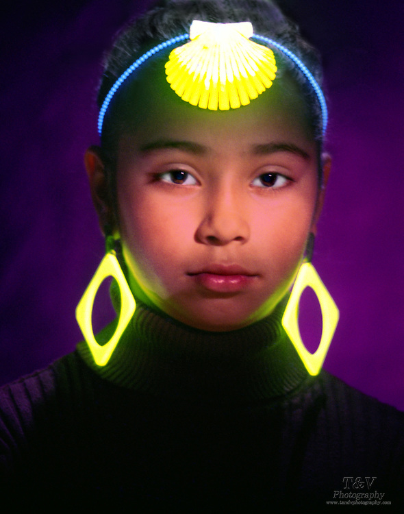 Portrait of a young girl with glowing ear rings and shell head band.Black light