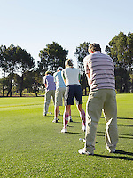 Golfers teeing off back view