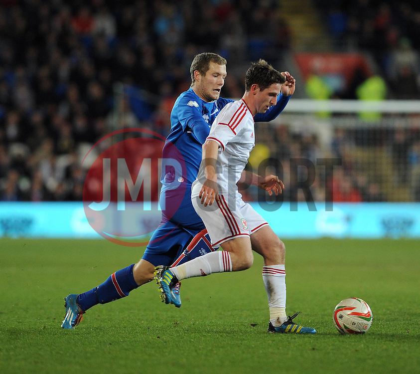Joe Allen of Wales (Liverpool) is challenged by Bjorn Daniel Sverrisson (Viking FK) of Iceland  - Photo mandatory by-line: Dougie Allward/JMP - Tel: Mobile: 07966 386802 03/03/2014 -