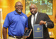 Roy Giles, left, is recognized as an Employee of the Month by Brian Busby, right, during a Houston ISD Board of Trustees meeting, June 8, 2017.