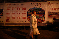 An ethnic Uighur woman walks past a propaganda banner in Urumqi city, Xinjiang Uighur Autonomous Province, China, 18 November 2017. Uighurs, a Muslim ethnic minority group in China, make up about 40 per cent of the 21.8 million people in Xinjiang, a vast, ethnically divided region that borders Pakistan, Afghanistan, Kazakhstan, Kyrgyzstan and Mongolia. Other ethnic minorities living in here include the Han Chinese, Kyrgyz, Mongolian and Tajiks people. Xinjiang has long been subjected to separatists unrests and violent terrorist attacks blamed by authorities on Islamist extremism while human rights groups say Chinese repression on religious rights, culture and freedom of movement caused undue tensions. Life however goes on under the watchful eye of the government for the ethnic Uighurs living in the city of Urumqi and surrounding areas and the region is still considered an attractive tourist spot. A recent report by state media Xinhua news agency claims Xinjiang received more than 100 million tourists in 2017, 'the highest figure in its history'.
