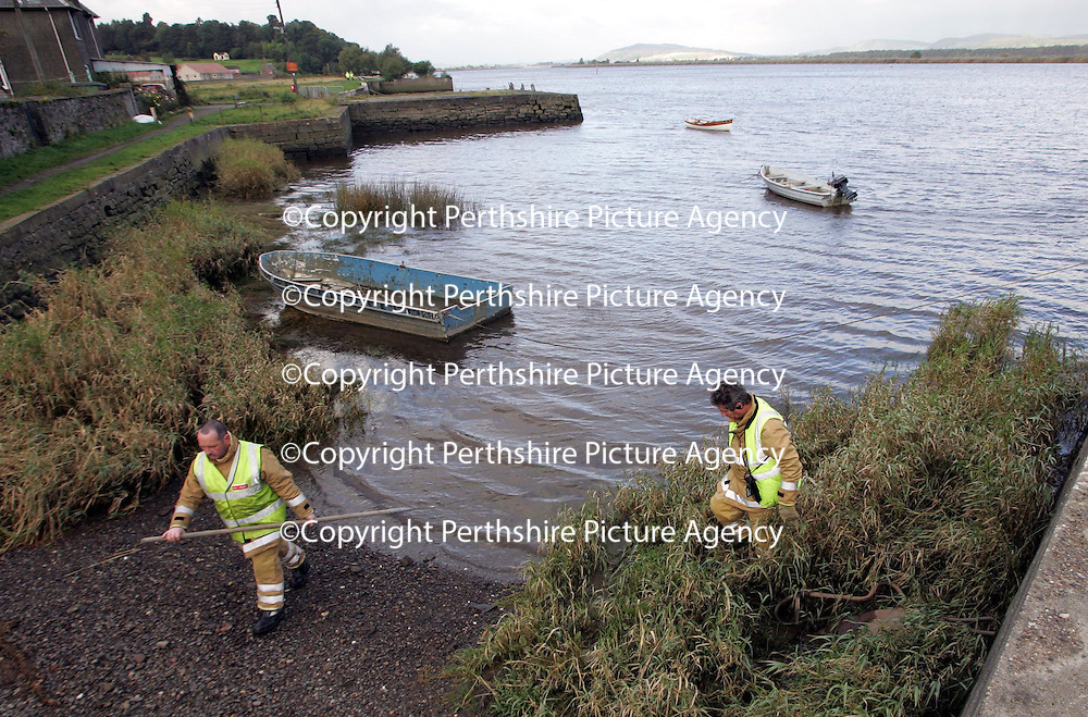 Firefighters searching the shorleine in Newburgh in Fife looking for 16 year old Michael Udall who slipped into the Firth of Tay from a pier last night whilst fishing with a friend. The pier that Michael fell from can be seen in the distance guarded by two police in yellow jackets.<br />Picture by Graeme Hart.<br />Copyright Perthshire Picture Agency<br />Tel: 01738 623350  Mobile: 07990 594431