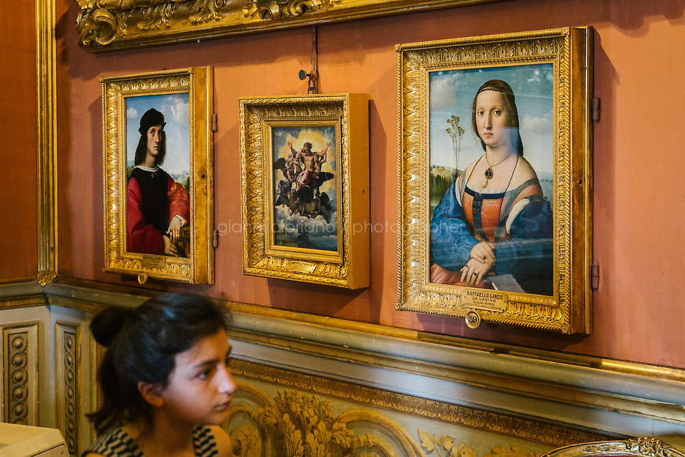 FLORENCE, ITALY - 3 JUNE 2018: A visitor walks by the dual portraits of Agnolo Doni and his wife Maddalena Strozzi, painted by Raphael round 1504-1505, here in the Hall of Saturn of Palazzo Pitti before the paintings will be relocated in room 41 of the Uffizi, in Florence, Italy, on June 3rd 2018.<br /> <br /> As of Monday June 4th 2018, Room 41 or the &ldquo;Raphael and Michelangelo room&rdquo; of the Uffizi is part of the rearrangement of the museum's collection that has<br /> been defining Uffizi Director Eike Schmidt&rsquo;s grander vision for the Florentine museum.<br /> Next month, the museum&rsquo;s Leonardo three paintings will be installed in a<br /> nearby room. Together, these artists capture &ldquo;a magic moment in the<br /> first decade of the 16th century when Florence was the cultural and<br /> artistic center of the world,&rdquo; Mr. Schmidt said. Room 41 hosts, among other paintings, the dual portraits of Agnolo Doni and his wife Maddalena Strozzi painted by Raphael round 1504-1505, and the &ldquo;Holy Family&rdquo;, that Michelangelo painted for the Doni couple a year later, known as the<br /> Doni Tondo.