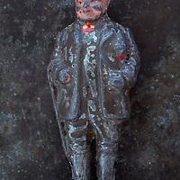 Worn lead model of rotund 19th century farmer standing against mottled metal background