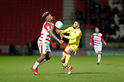 Mallik Wilks of Doncaster Rovers challenges for the ball with Tareiq Holmes-Dennis of Bristol Rovers during the EFL Sky Bet League 1 match between Doncaster Rovers and Bristol Rovers at the Keepmoat Stadium, Doncaster, England on 26 March 2019.
