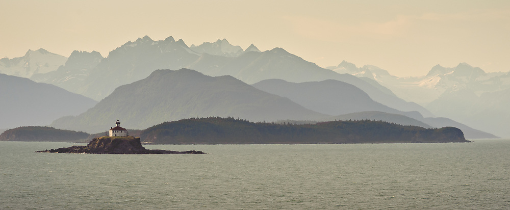 The mountains of the Chilkat Range serve as a backdrop for evening sunlight on the Eldred Rock Lighthouse, located on the Lynn Canal in southeast Alaska. Construction of the lighthouse was finished in 1906 after shipwrecks occurred in the area during the 1898 Klondike gold rush. The light was automated by the U.S. Coast Guard in 1973 with the original fourth-order Fresnel lens moved to the Sheldon Museum in Haines.