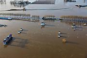 Nederland, Limburg, Gemeente Venlo, 10-01-2011. Het sluis en stuwcomplex Belfeld bij hoogwater van de Maas. Het hoogwater Maas is een gevolg van sneeuwsmelt en neerslag in de bovenloop van de rivier. De stuw is gestreken en de scheepvaart kan  gebruik maken van de vaargeul naast de stuwtorens. De schutsluizen staan geheel onder water, de bedieningsgebouwen staan op kolommen boven het water. Het complex is gebouwd in het kader van de kanalisatie van de Maas in de jaren 1918 - 1929..Lock and weir complex Belfeld at high waters of river Meuse. The flood is due to snow melt and precipitation upstream. The weir is 'lifted' allowing for ships to pass. The normal shipping locks lock are completed flooded (and under water). The control buildings are build on columns. The whole complex was built in the context of the canalization of the Meuse in the years 1918 to 1929..luchtfoto (toeslag), aerial photo (additional fee required).© foto/photo Siebe Swart