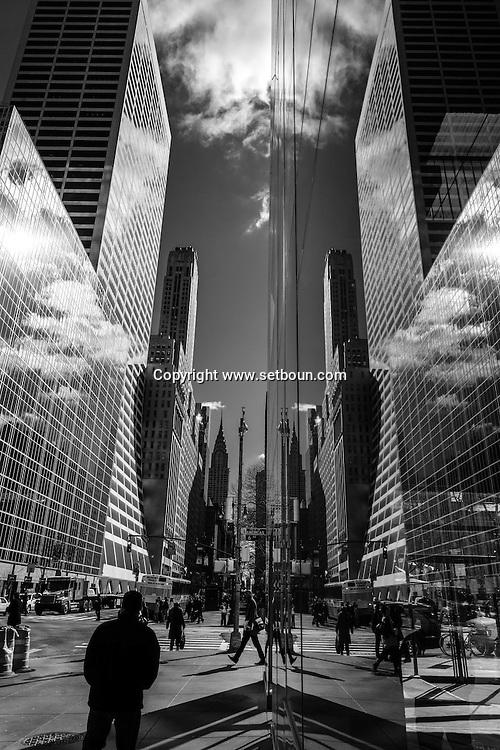 New York -  pedestriens on 42nd street. Mirror reflection, a corridor beetween skyscrappers.
