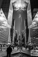 New York -  pedestriens on 42nd street. Mirror reflection, a corridor beetween skyscrappers.