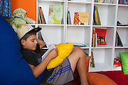 Bruno reading a book on the floor of the community library, Biblioteca Comunitaria do Arquipelago, Porte Alegre, Brazil. <br /> <br /> Cirandar is working in partnership with  C&A and C&A Instituto to implement a network of Community Libraries in eight communities of Porto Alegre.