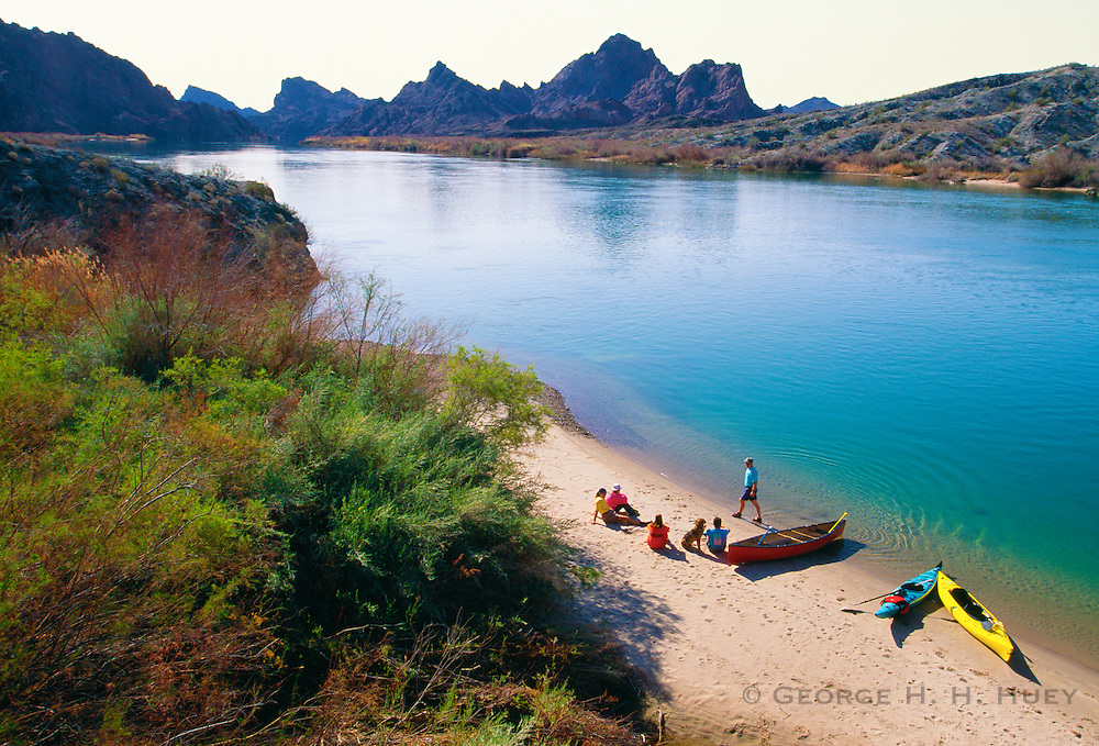 350166-1010 ~ Copyright: George H. H. Huey ~ Canoes and kayak in Topock Gorge, Colorado River with visitors on beach. Needles Wilderness in background. Havasu National Wildlife Refuge, Arizona.