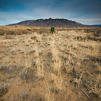 man standing within the landscape.  taken at the sandia mountains, new mexico.  vertical composition with copy space.