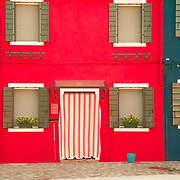 images of the colorful buildings of the island of Burano, Venice and their reflections onto the canals