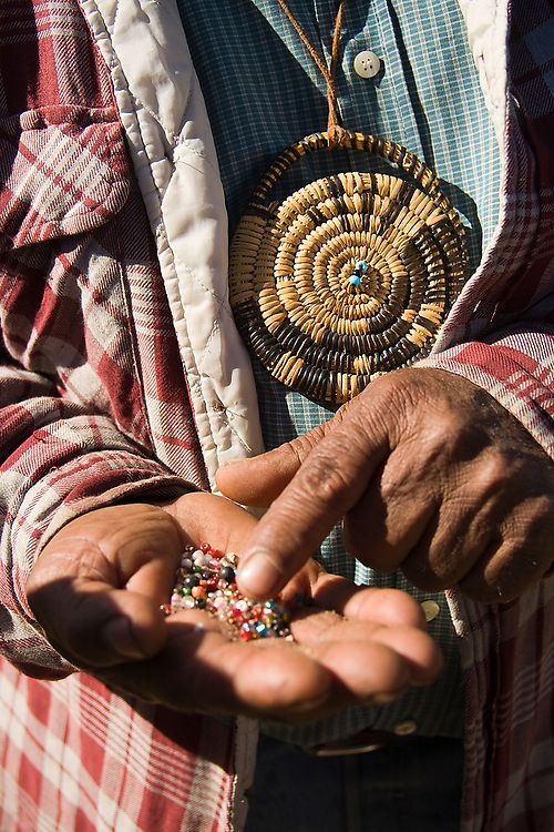 A Kumiai indian man picks through colorful plastic beads used in jewelry in the indigenous village of San Antonio Necua, Baja California Norte, Mexico. His pendant, believed to provide protection, is made of tightly woven pine needles, a basket weaving technique traditional to the Kumiai people.